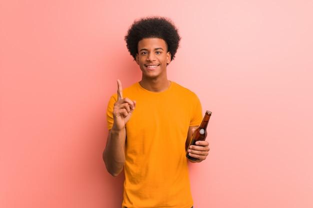 Joven afroamericano sosteniendo una cerveza mostrando número uno