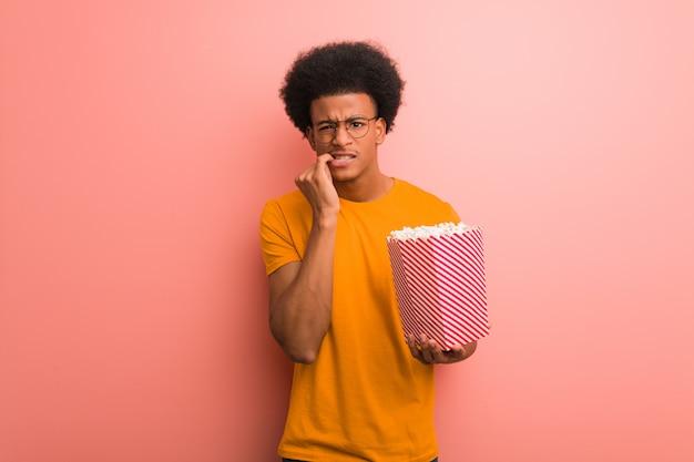 Joven afroamericano sosteniendo un cubo de palomitas de maíz mordiendo las uñas, nervioso y muy ansioso