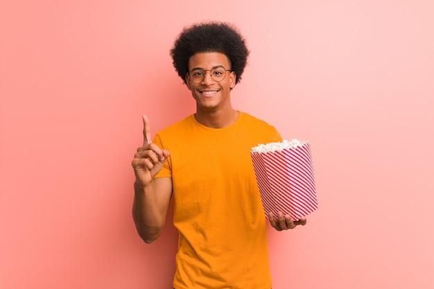 Joven afroamericano sosteniendo un cubo de palomitas de maíz que muestra el número uno