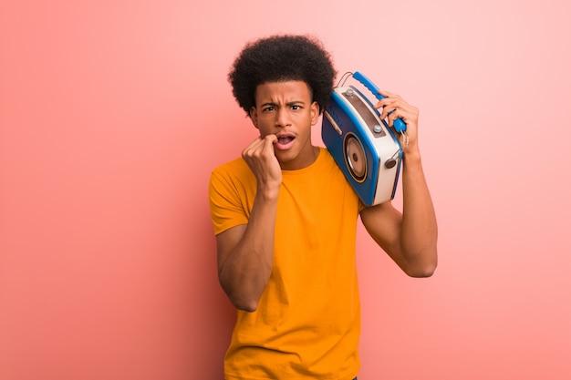 Joven afroamericano sosteniendo una radio vintage mordiéndose las uñas, nervioso y muy ansioso