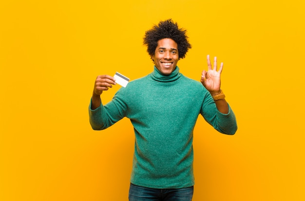 Joven afroamericano con una tarjeta de crédito contra naranja