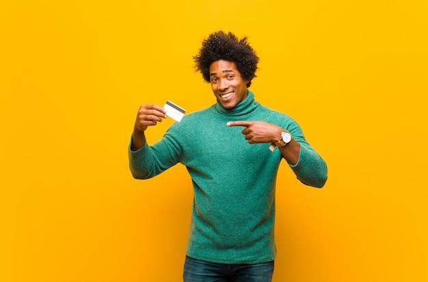 Joven afroamericano con una tarjeta de crédito naranja