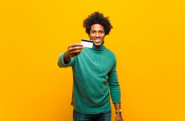 Joven afroamericano con una tarjeta de crédito en naranja