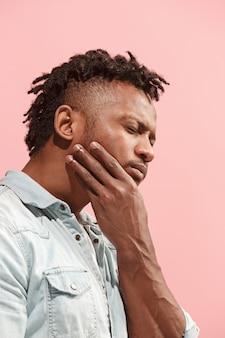 Un joven afroamericano tiene dolor de muelas.