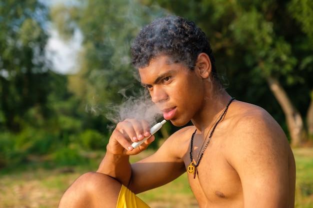Joven afroamericano vaping e-cigarrillo con e-líquido y exhala vapor o vapor al aire libre en verano. concepto de vapeo