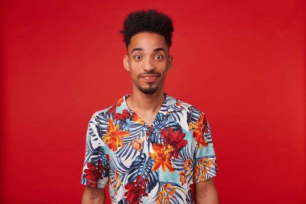 Joven afroamericano viste con camisa hawaiana, mira a la cámara y sonríe tranquila, se encuentra sobre fondo rojo.