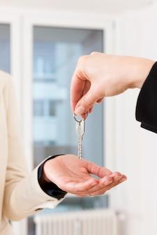 Joven agente de bienes raíces es con llaves en un apartamento