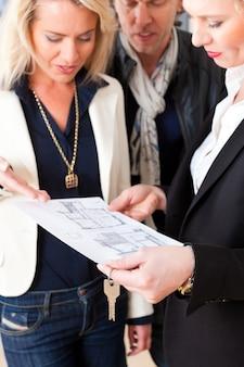 Joven agente de bienes raíces explica contrato de arrendamiento para pareja