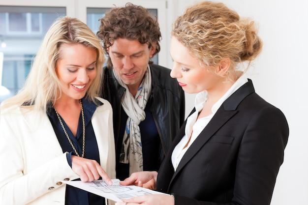 Joven agente de bienes raíces explicando el plano de la pareja