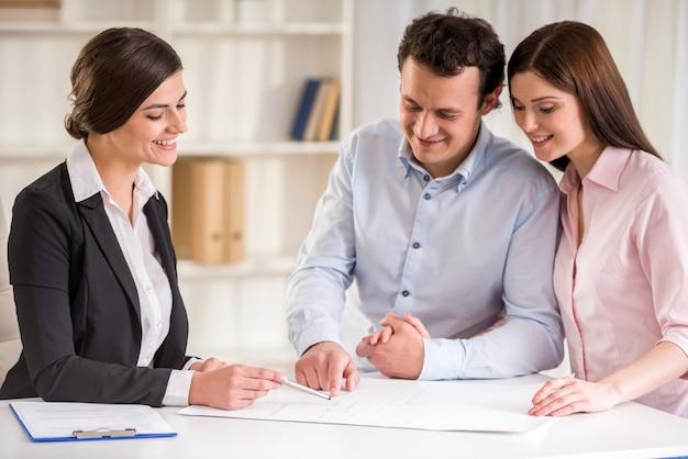 Joven agente de bienes raíces explicar el contrato de arrendamiento a la joven pareja.