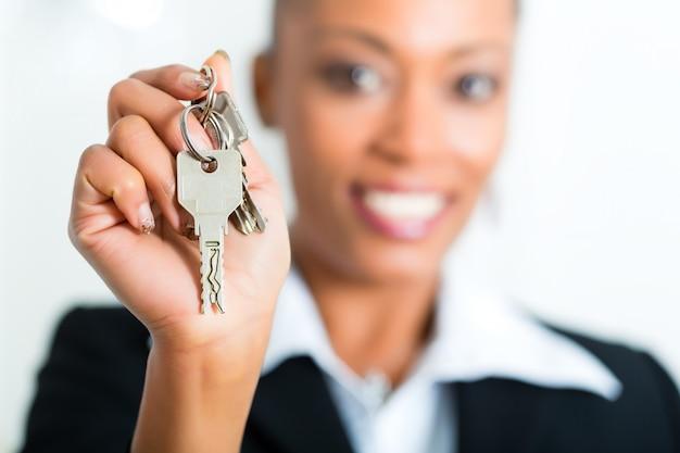 Joven agente de bienes raíces con llaves en un apartamento