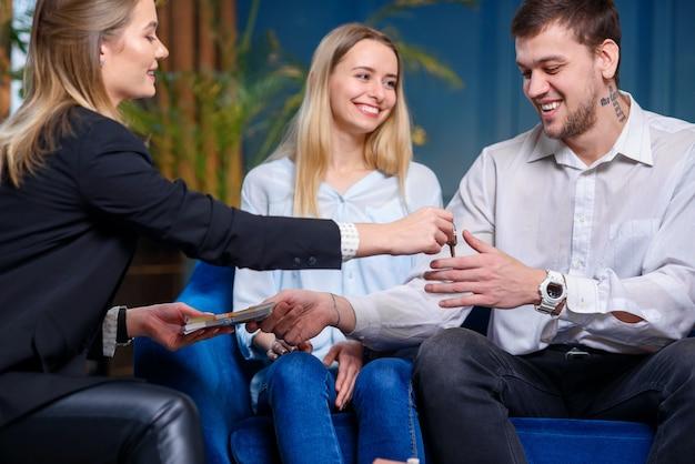 Joven agente de bienes raíces que da la llave del piso, la casa a la joven pareja mientras que el cliente masculino da dinero.
