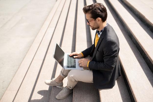 Joven agente elegante con dispositivo móvil sentado en las escaleras en un día soleado mientras navega en la red durante el trabajo sobre el proyecto