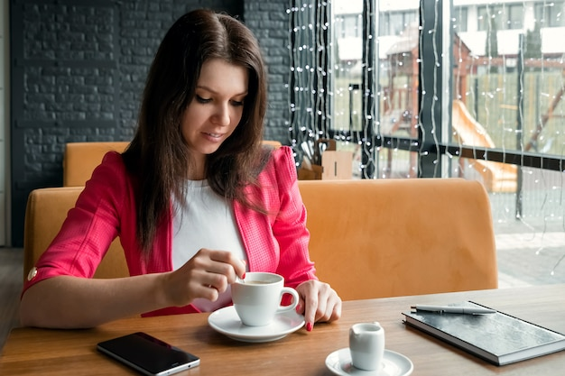 Una joven agita azúcar en una taza de café, se sienta en una cafetería detrás de un stolikos de madera
