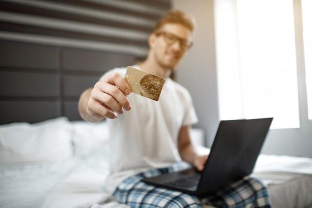 Joven agradable sentarse en la cama temprano en la mañana. muestra tarjeta de crédito en la cámara. chico espera portátil. dinero electrónico.