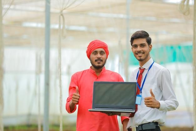 Joven agricultor indio y agrónomo mostrando golpes con portátil en invernadero