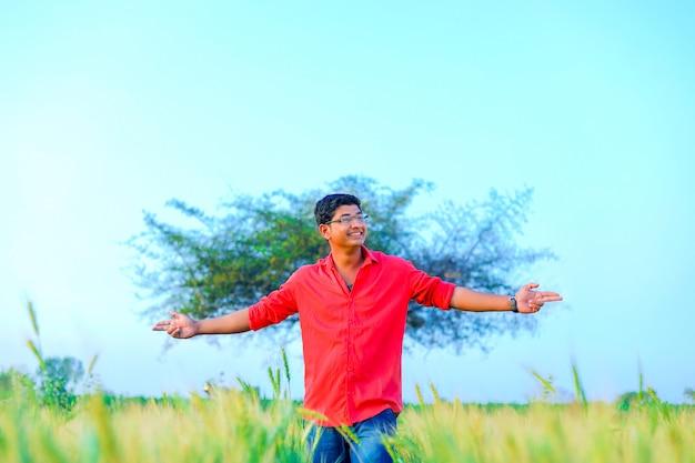 Joven agricultor indio en el campo de trigo
