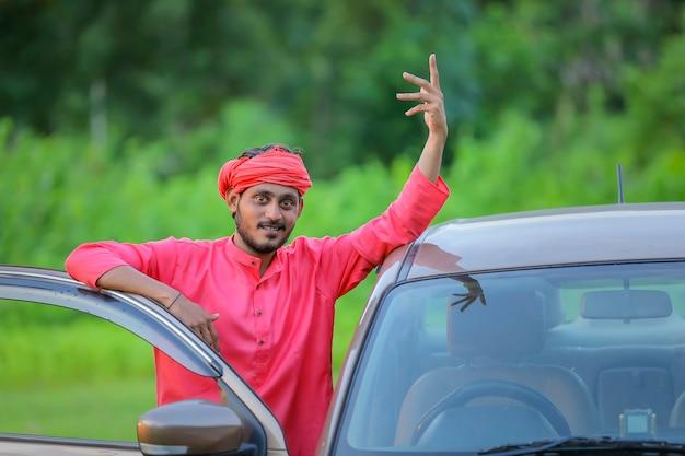 Joven agricultor indio con coche nuevo