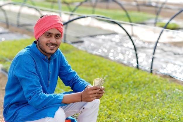 Joven agricultor indio contando y mostrando dinero en invernadero