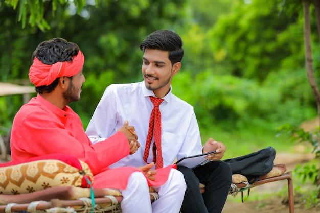 Joven agricultor indio firmar en documento con banquero en casa