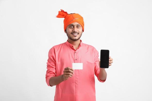 Joven agricultor indio mostrando la tarjeta y el teléfono inteligente sobre fondo blanco.