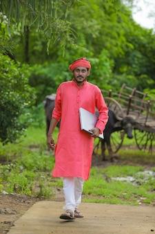 Joven agricultor indio con portátil en el campo