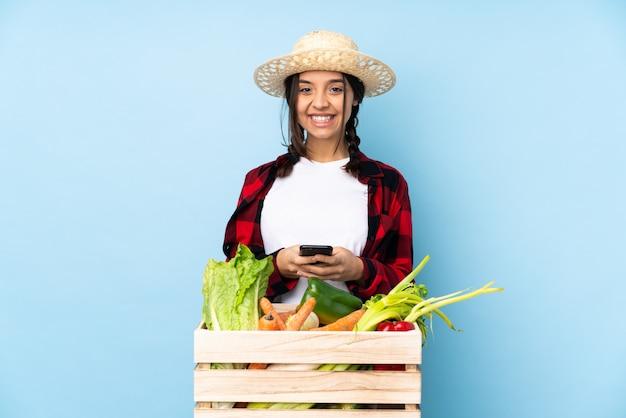 Joven agricultor mujer sosteniendo verduras frescas en una canasta de madera enviando un mensaje con el móvil