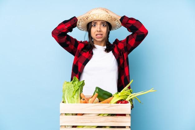 Joven agricultor mujer con verduras frescas en una canasta de madera frustrado y toma las manos sobre la cabeza