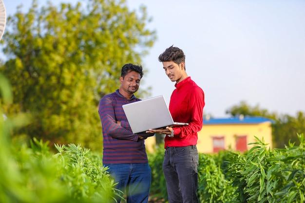 Joven agrónomo analizando campo con agricultor, agricultura india