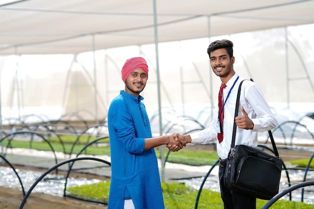 Joven agrónomo indio con agricultor en invernadero