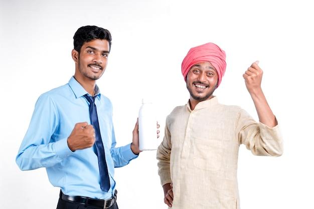 Joven agrónomo indio dando botella al agricultor sobre fondo blanco.