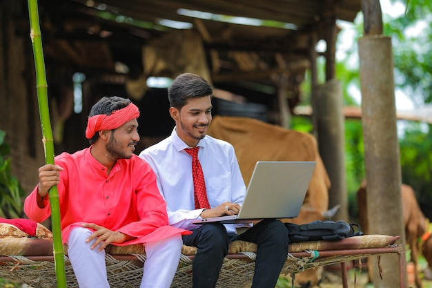 Joven agrónomo indio mostrando alguna información al agricultor en la computadora portátil en casa