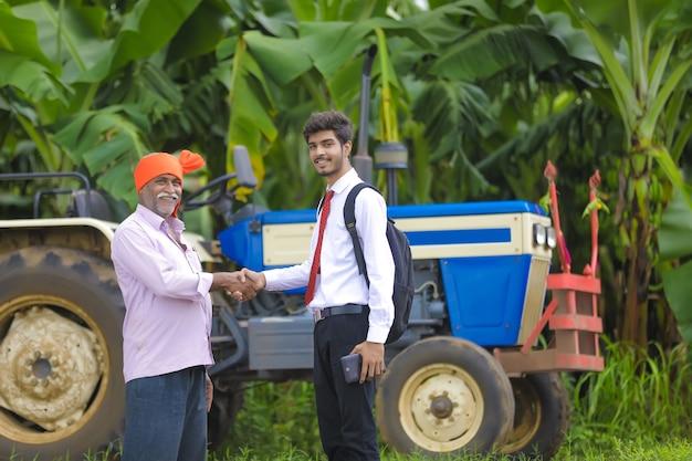 Joven agrónomo indio shack mano con agricultor en campo