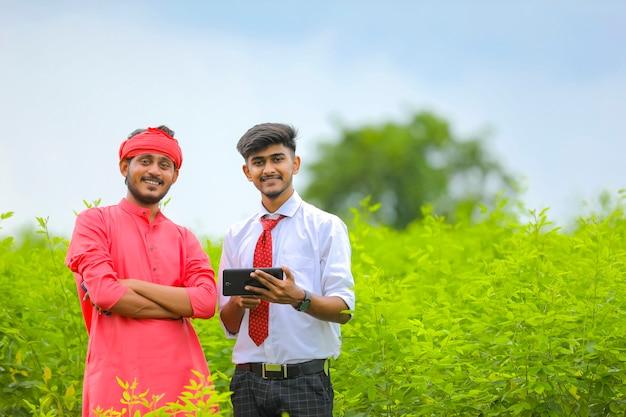 Joven agrónomo mostrando alguna información en tableta al agricultor en campo verde