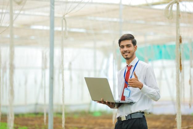 Joven agrónomo o banquero con portátil en invernadero