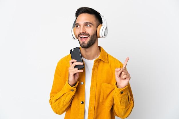 Joven aislado en la pared blanca escuchando música con un móvil y cantando