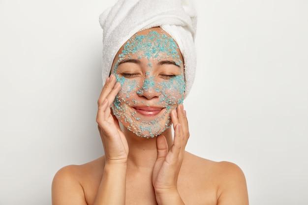 Joven alegre aplica exfoliante natural en la cara, toca las mejillas, mantiene los ojos cerrados, usa una toalla, se somete a procedimientos de belleza después de la ducha, modela en interiores. modelo femenino con sal marina azul en la piel