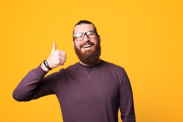 Joven alegre barbudo con gafas está sonriendo a la cámara y mostrando un pulgar hacia arriba