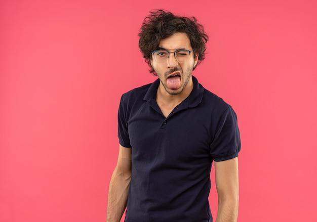 Joven alegre en camisa negra con gafas ópticas, parpadea y saca la lengua aislada en la pared rosa