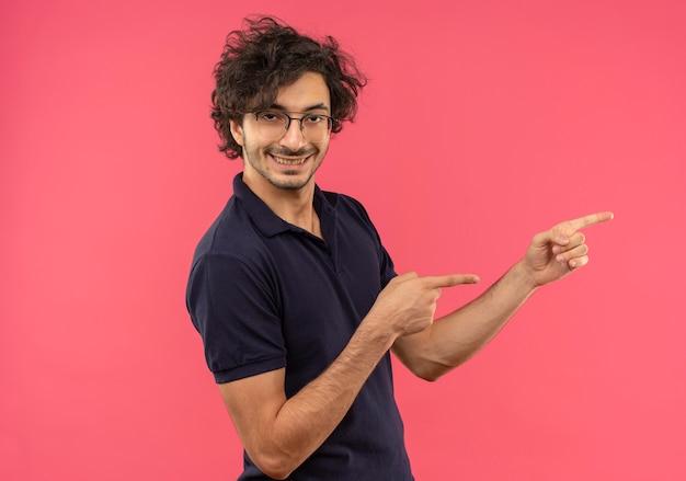 Joven alegre en camisa negra con lentes ópticos apunta al lado y parece aislado en la pared rosa