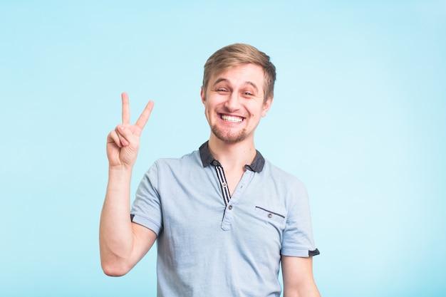 Joven alegre en camiseta de polo mostrando el signo de la victoria y sonriendo