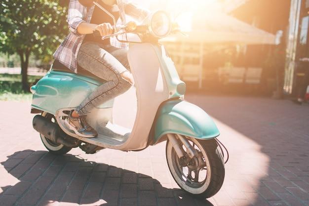 Joven alegre conduciendo scooter en la ciudad de