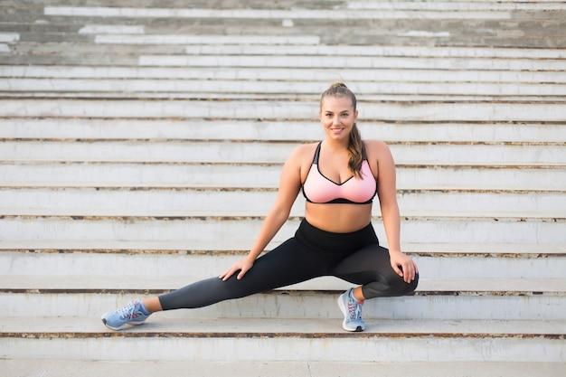 Joven alegre dama de talla grande en top deportivo y mallas haciendo deporte en las escaleras mientras está felizmente al aire libre