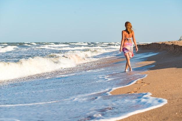 Joven alegre disfruta de las olas tormentosas en la orilla del mar