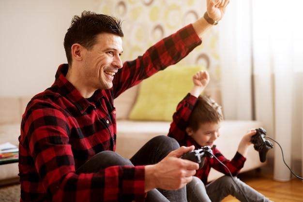 Joven alegre emocionado padre e hijo en la misma camisa roja jugando juegos de consola con gamepads en una luminosa sala de estar.