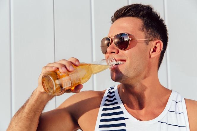 Joven alegre en gafas de sol bebiendo cerveza 66bb2f19ed79