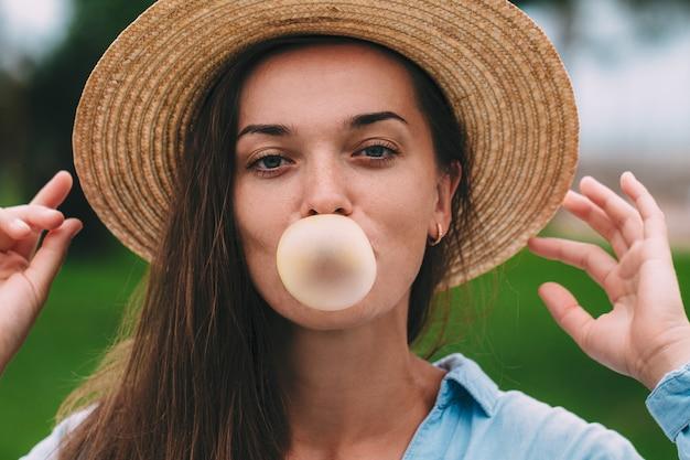 Joven alegre feliz hipster mujer con sombrero soplando burbujas de chicle al aire libre