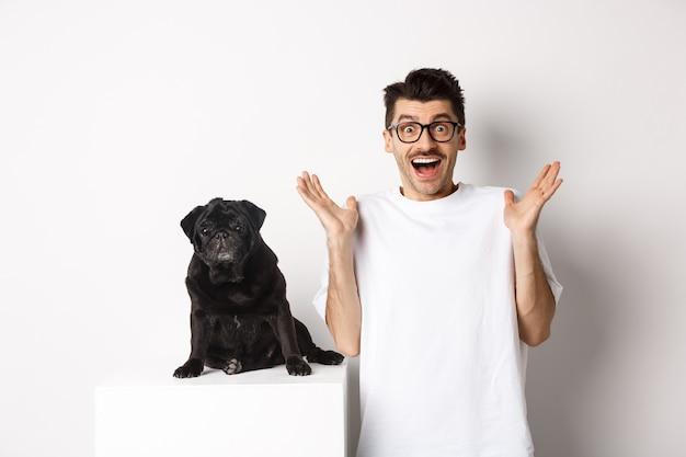 Joven alegre con gafas de pie con su mascota, regocijándose y mirando a la cámara divertido, escucha una gran noticia, de pie con pug sobre fondo blanco.