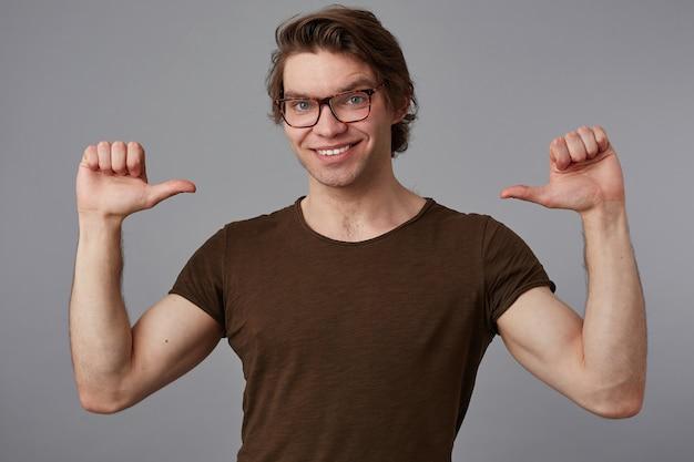 Un joven alegre con gafas viste una camiseta en blanco de pie sobre un fondo gris y se señala a sí mismo, se ve feliz y sonríe ampliamente y dice