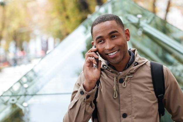 Joven alegre hablando por su teléfono en la calle
